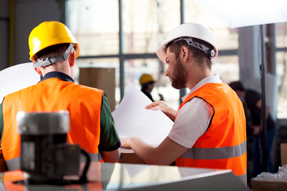 Male factory worker and supervisor are analyzing plans