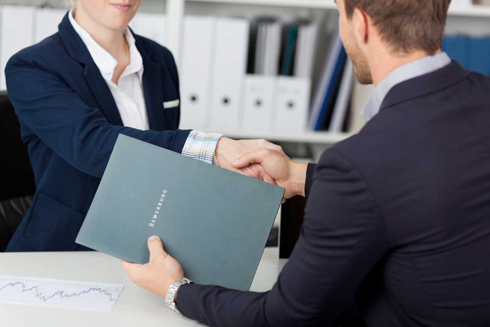 Midsection of a businessman shaking hands with a female interviewer in office